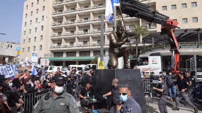 Artist chains himself to statue in anti-Netanyahu protest in Jerusalem